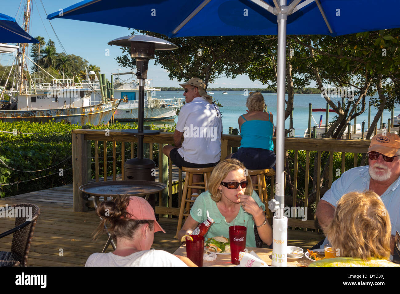 Port Charlotte en Floride Pêche Placida Harbour Restaurant restaurant Gasparilla Bay Golfe du Mexique Table de salle à manger en plein air des parapluies homme femme couple co Photo Stock