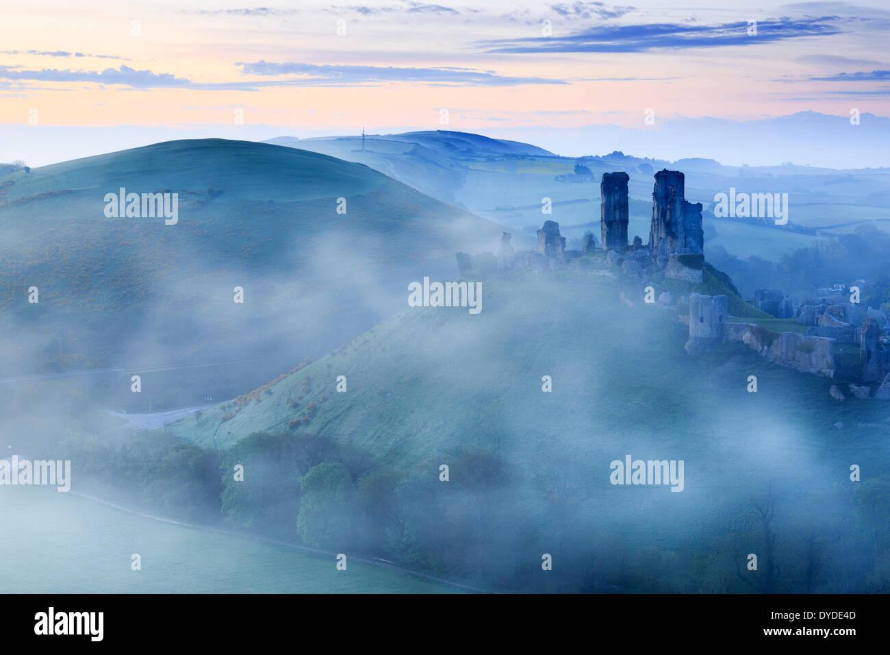 Château de Corfe à Dorset s'élevant au-dessus du brouillard tôt le matin. Photo Stock