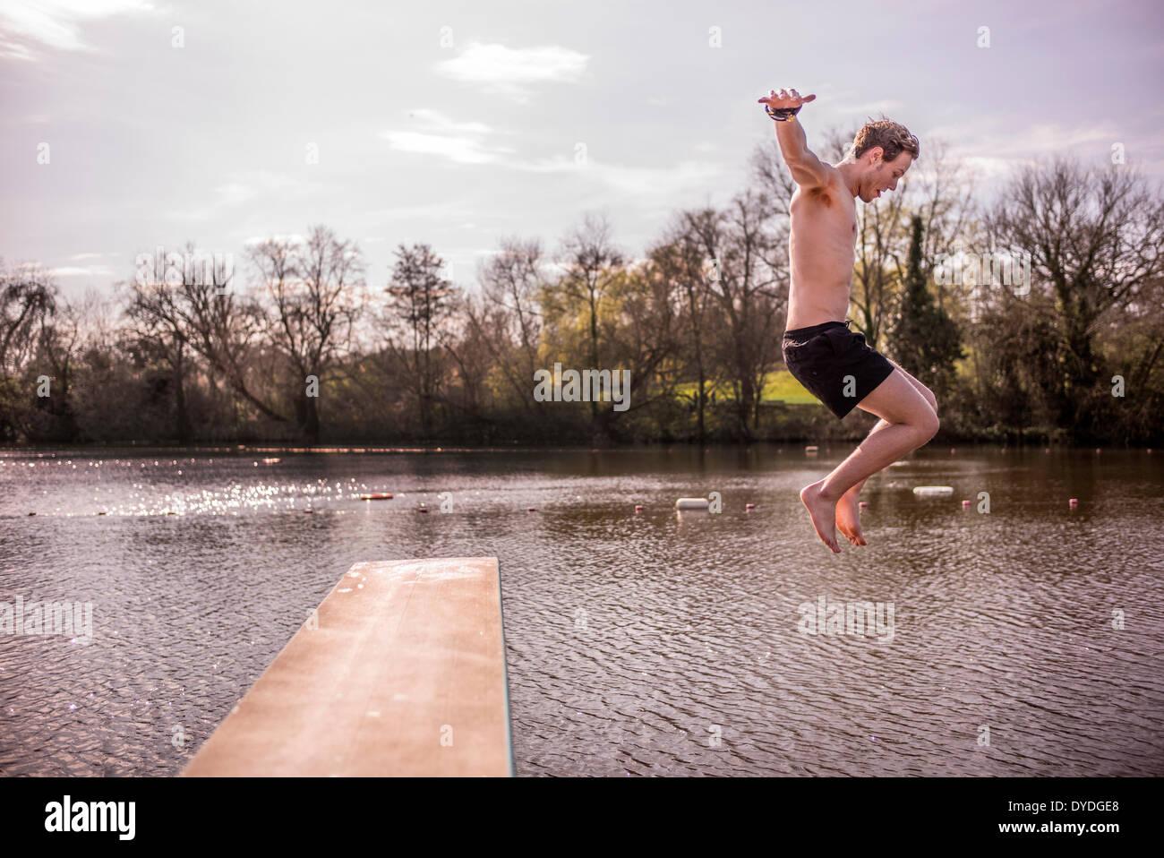 Un jeune homme en maillot de sauter dans l'eau douce de printemps des étangs. Photo Stock
