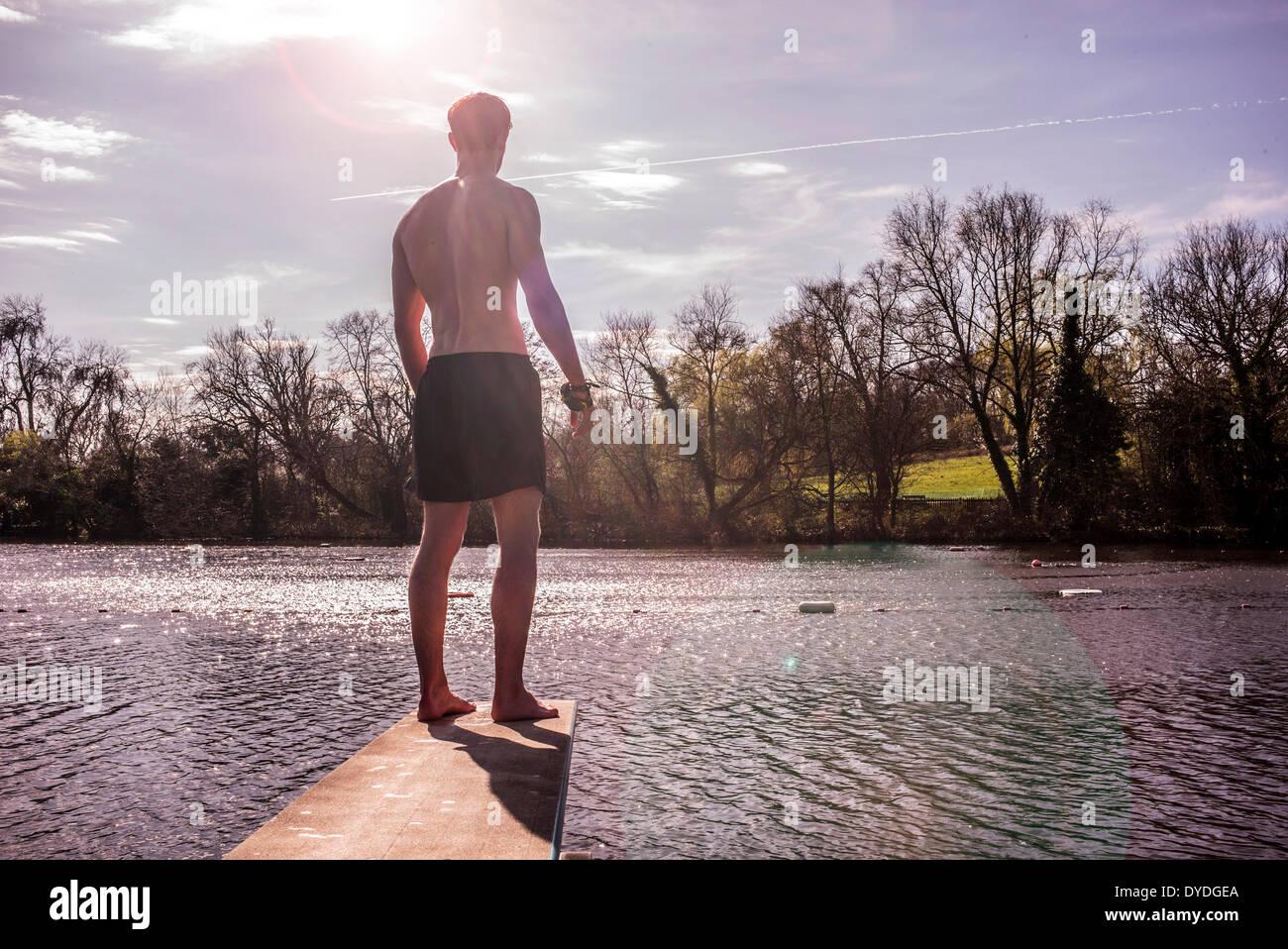 Un jeune homme en maillot de bain à côté des étangs d'eau douce de printemps. Photo Stock