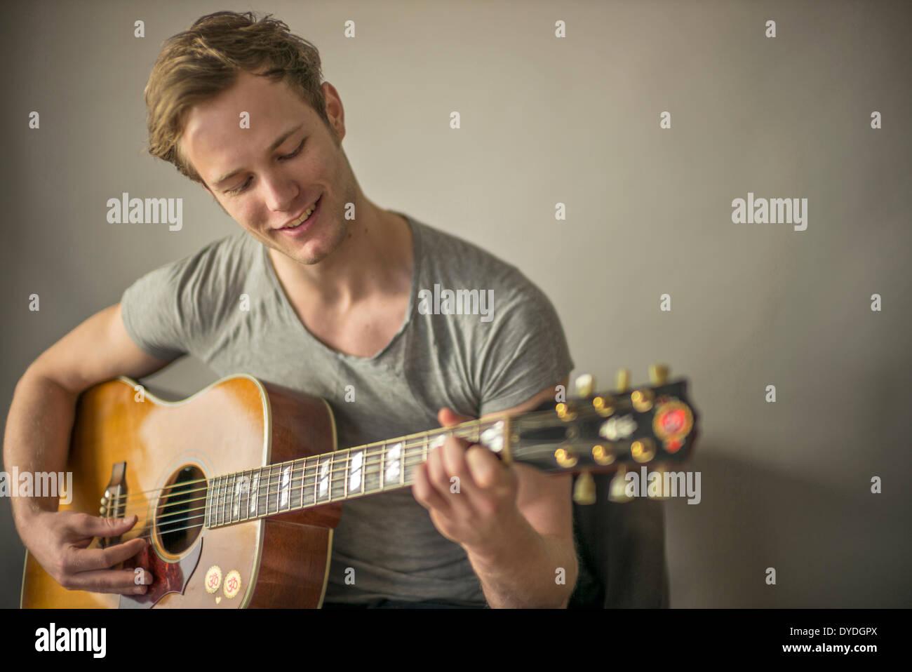 Un beau jeune homme jouant de la guitare acoustique. Photo Stock