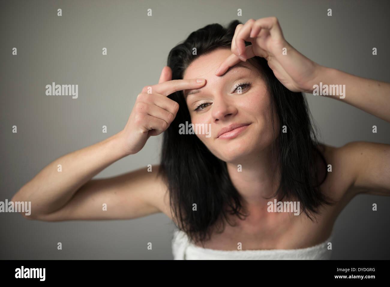 Une belle fille espiègle serrant son front. Photo Stock