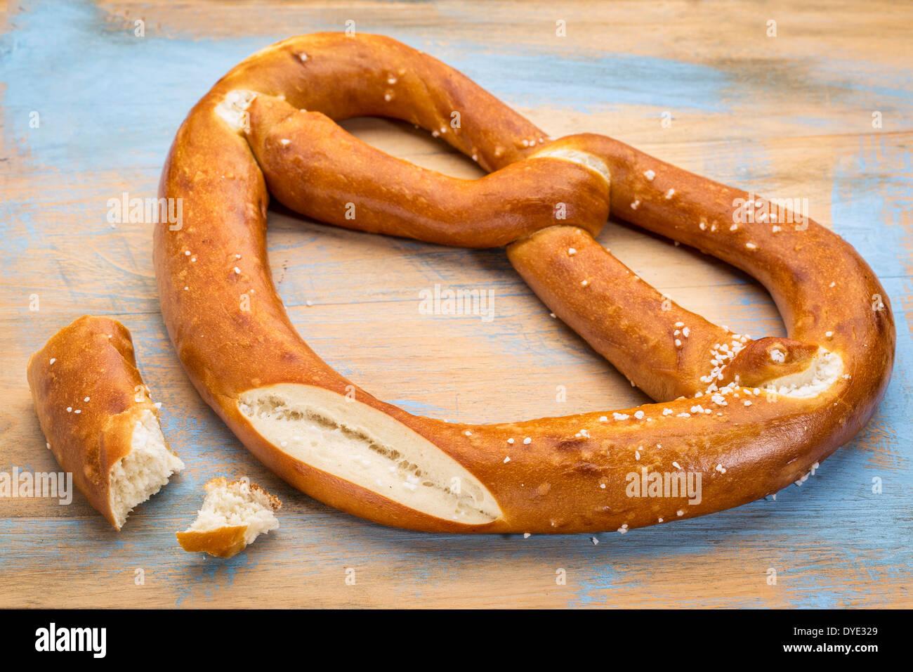 Un gros bretzel twist avec du sel sur une planche à découper en bois peint Photo Stock
