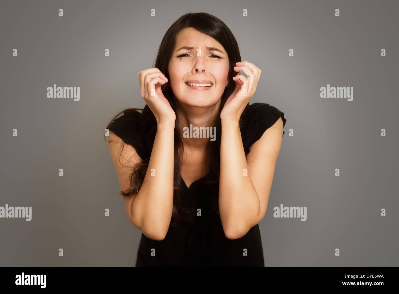 Jeune femme en pleurs éperdus avec elle les mains jointes dans l'angoisse debout avec les yeux baissés contre un fond studio blanc Photo Stock