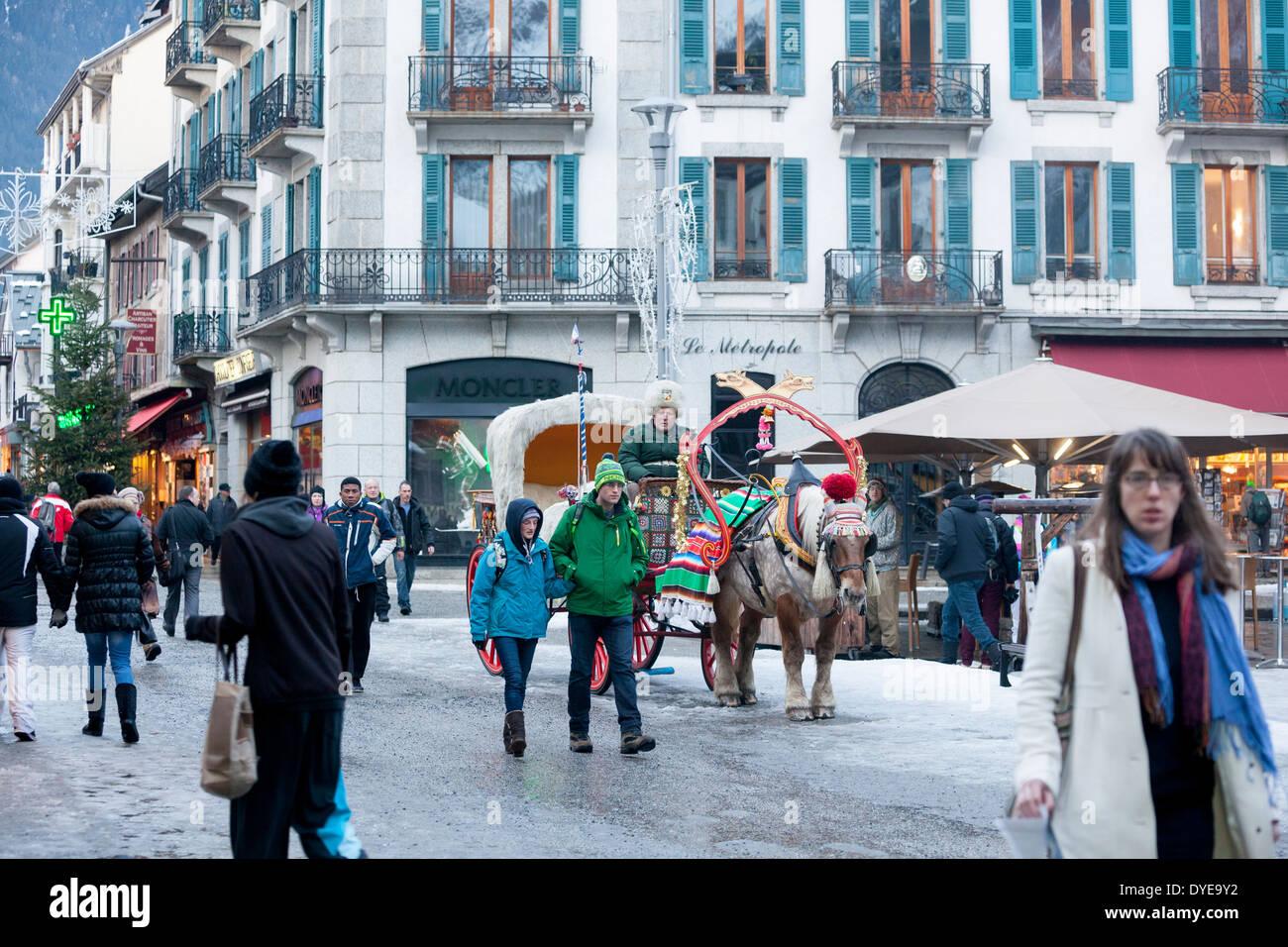 Les piétons passent devant un cheval dessiné buggy recouvert de fourrure sur la rue du Docteur Paccard dans le village de Chamonix Mont-Blanc. Photo Stock