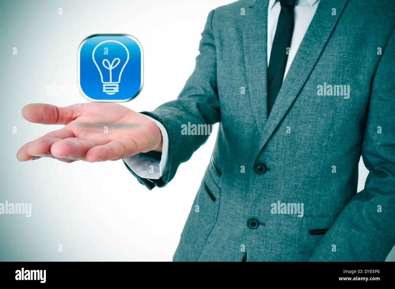 Un homme portant un costume avec une icône avec une ampoule dans la main Photo Stock