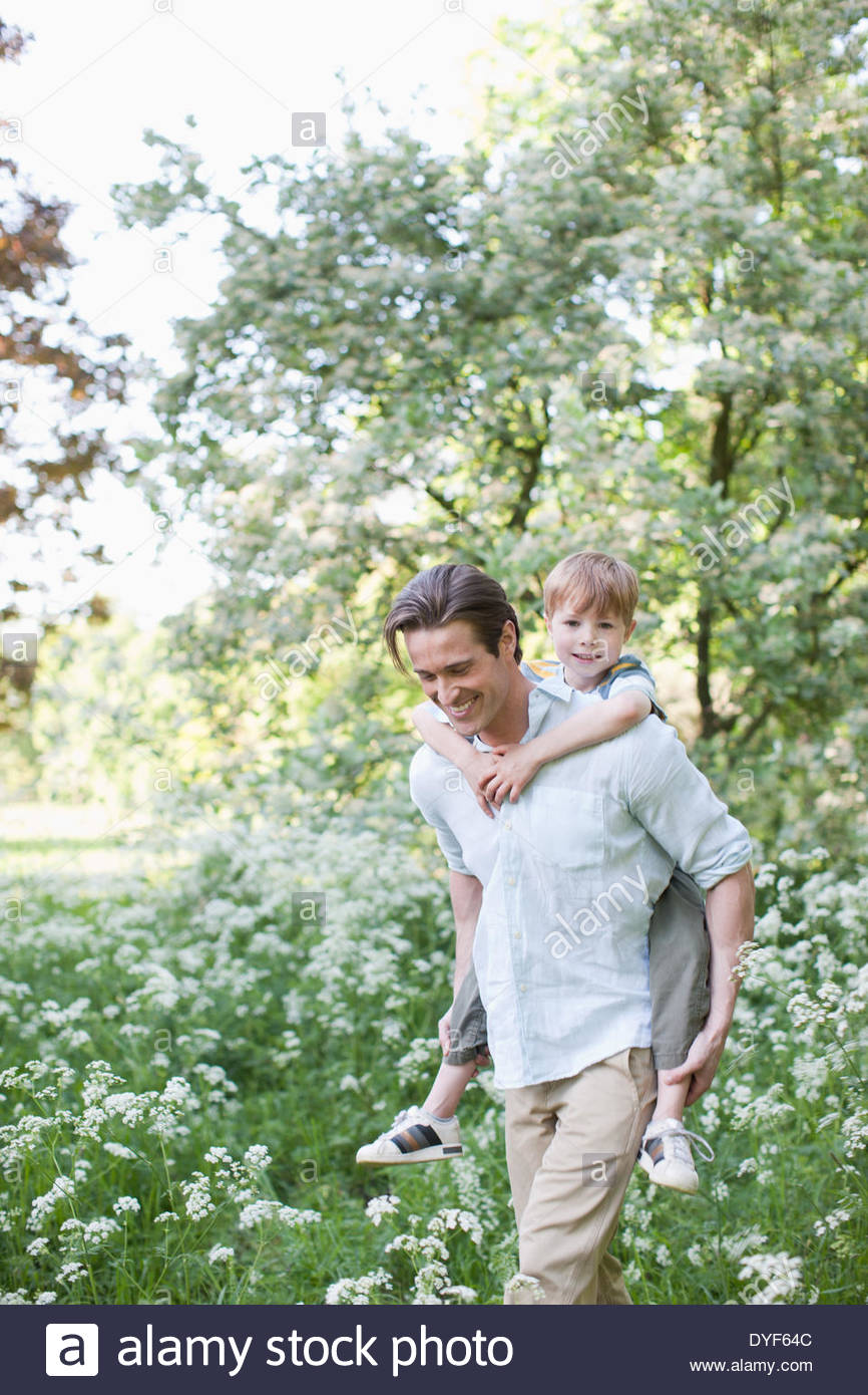 Father carrying son piggyback in park Photo Stock