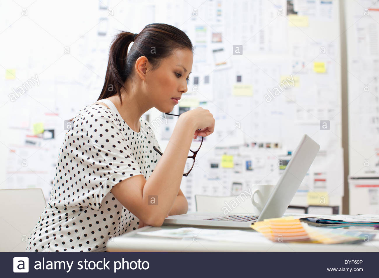 Serious businesswoman looking down laptop in office Photo Stock