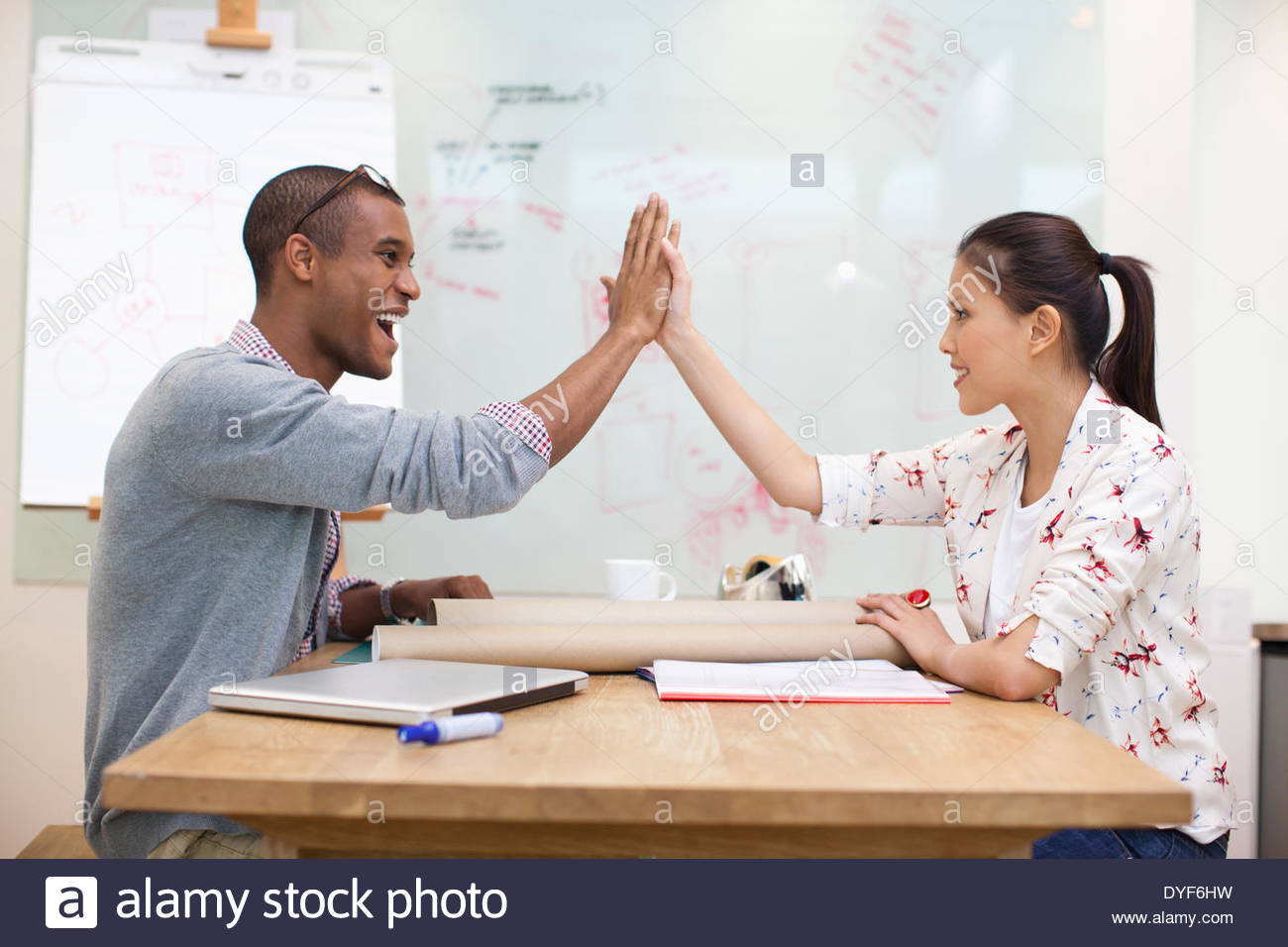 Les gens d'affaires high fiving in office Photo Stock