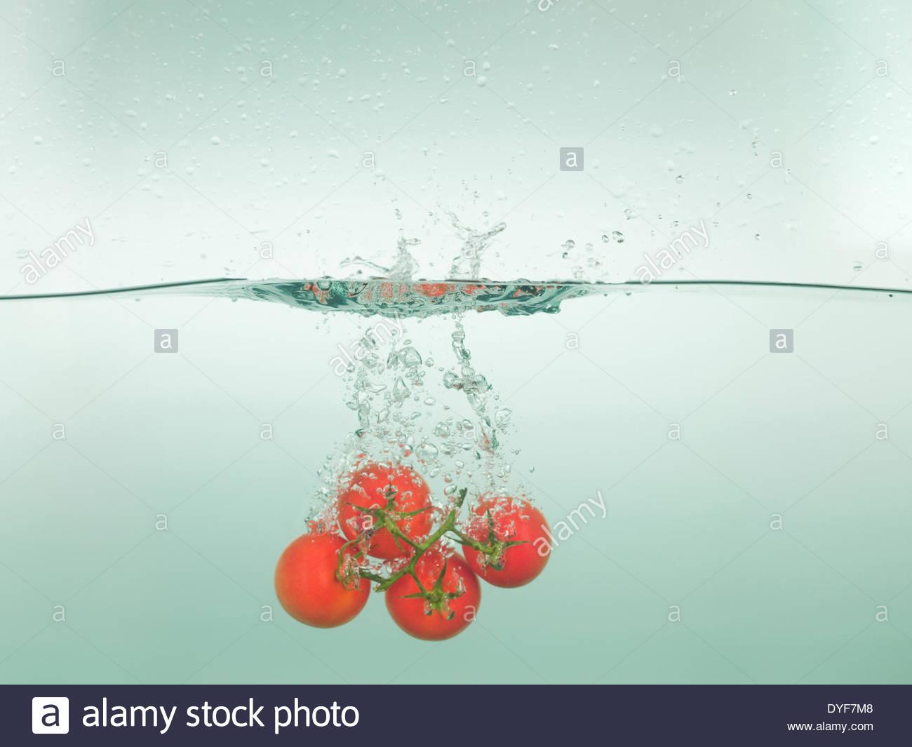 Les tomates splashing in water Photo Stock
