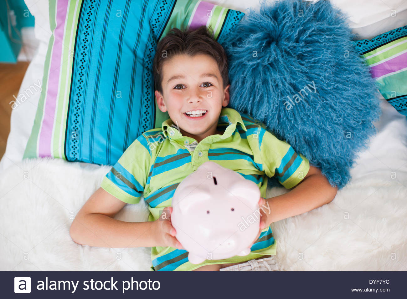 Boy laying in bed with piggy bank Photo Stock