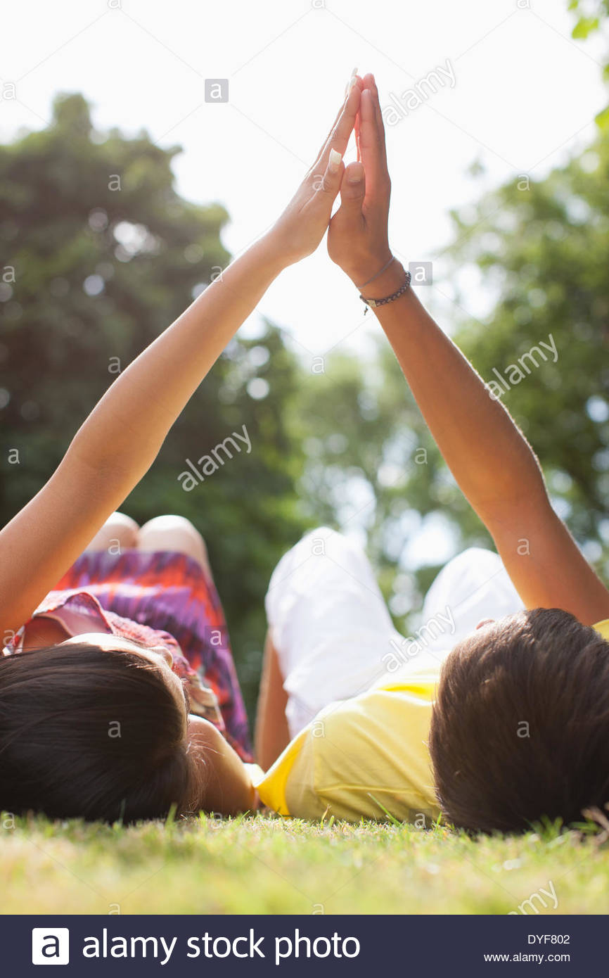 Les adolescents laying in grass holding hands Photo Stock