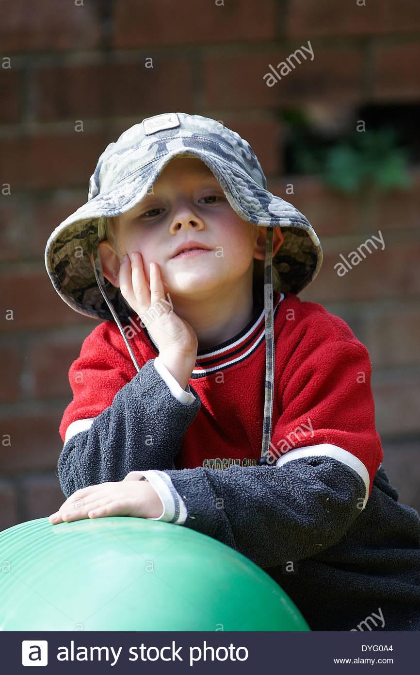 Un petit garçon portant un chapeau, s'appuyant sur une balle Pilates vert, à la recherche dans l'appareil photo sévèrement; prise lors d'un play-pause, à l'âge préscolaire, NSW, Australie. Photo Stock