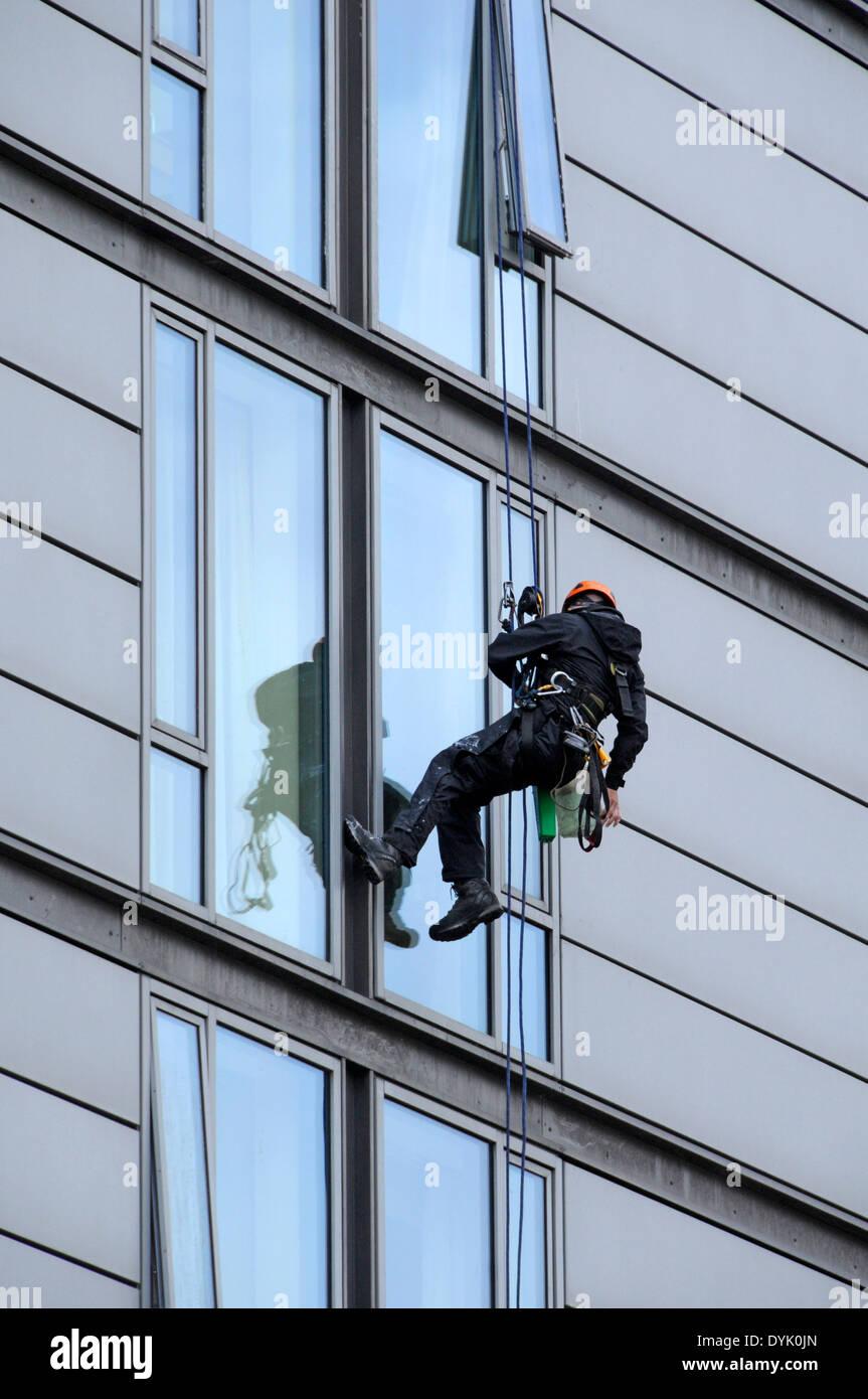 Nettoyant industriel à l'aide de techniques d'accès sur corde en plein travail sur un immeuble de bureaux, London Road, Manchester, England, UK Photo Stock