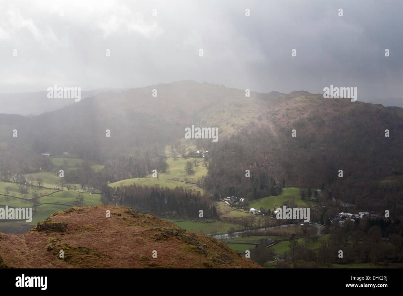 Les nuages de tempête passant sur Loughrigg tombe illuminée par la lumière du soleil entre les arbres d'Ambleside Banque D'Images