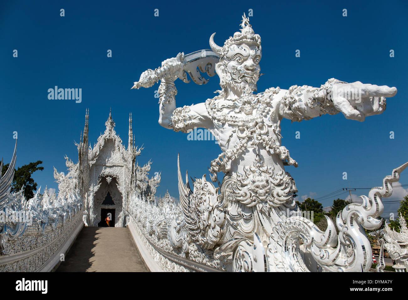 Wat Rong Khun, orné d'un tuteur et de démon sur le pont du Temple blanc par l'architecte et artiste Chalermchai Kositpipat Photo Stock