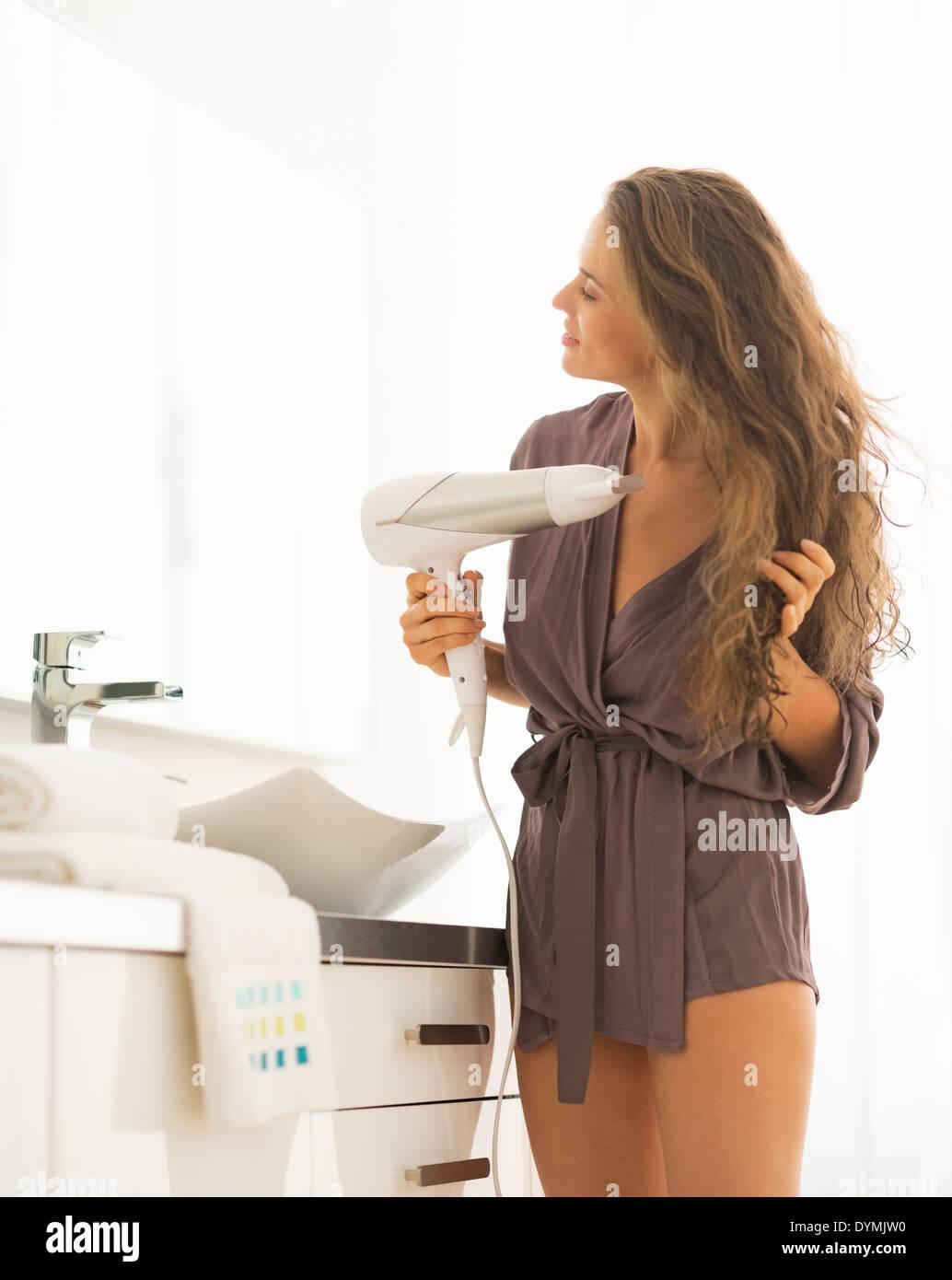 Jeune femme cheveux séchage coup dans la salle de bains Photo Stock
