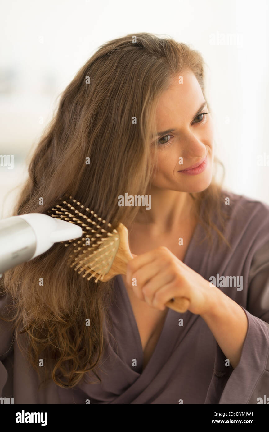 Jeune femme blow drying hair Photo Stock