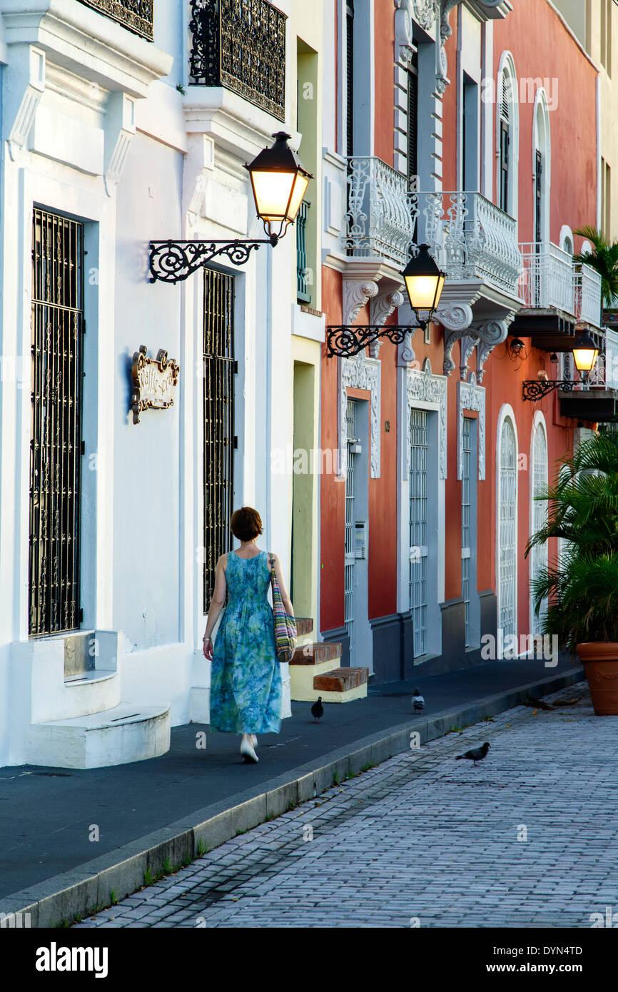 Femme marche par façades colorées et des lampes, Old San Juan, Puerto Rico Photo Stock
