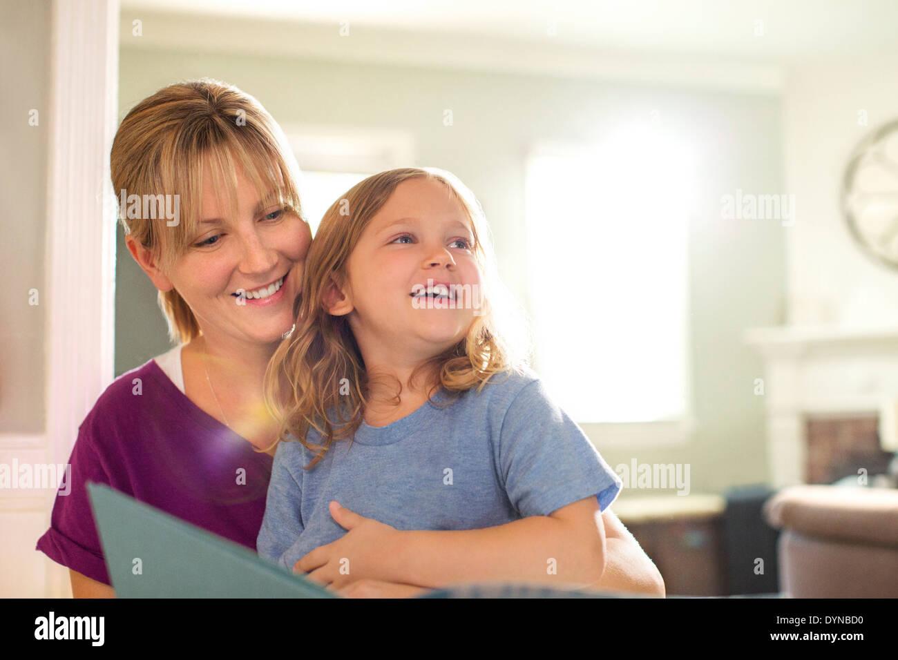 Mère et fille dans le salon de lecture Banque D'Images