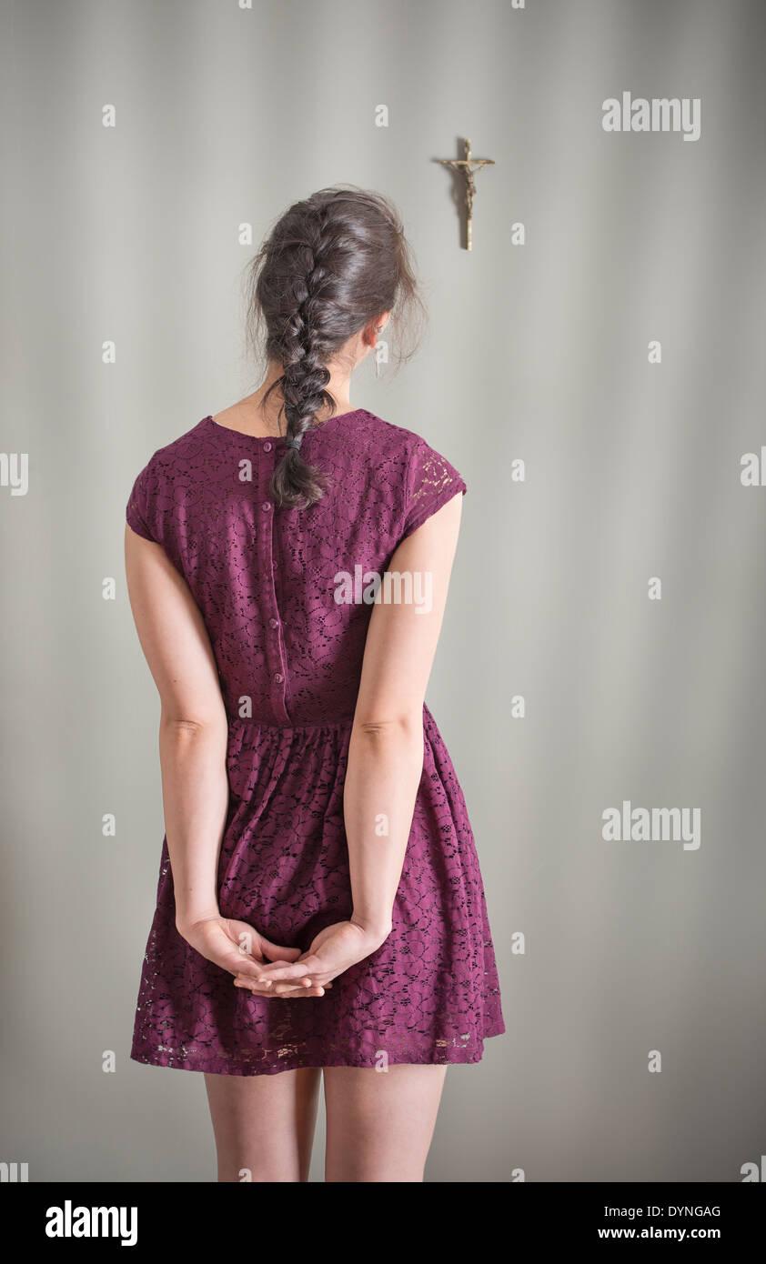 Vue arrière de woman looking at crucifix accroché au mur Photo Stock