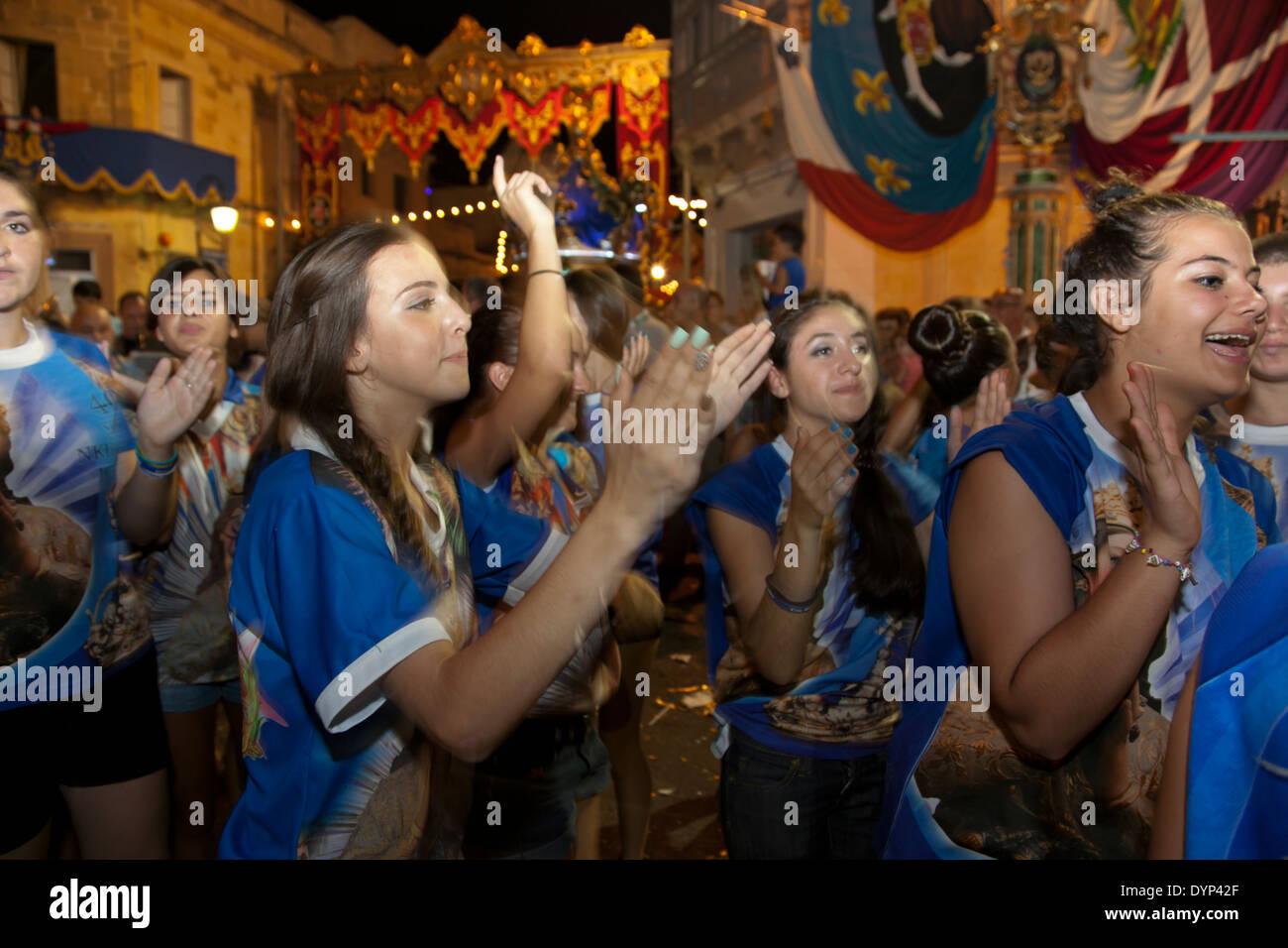 Les jeunes femmes clap et de la danse à la musique de fanfare au cours d'une ville traditionnelle fête à Malte. Photo Stock