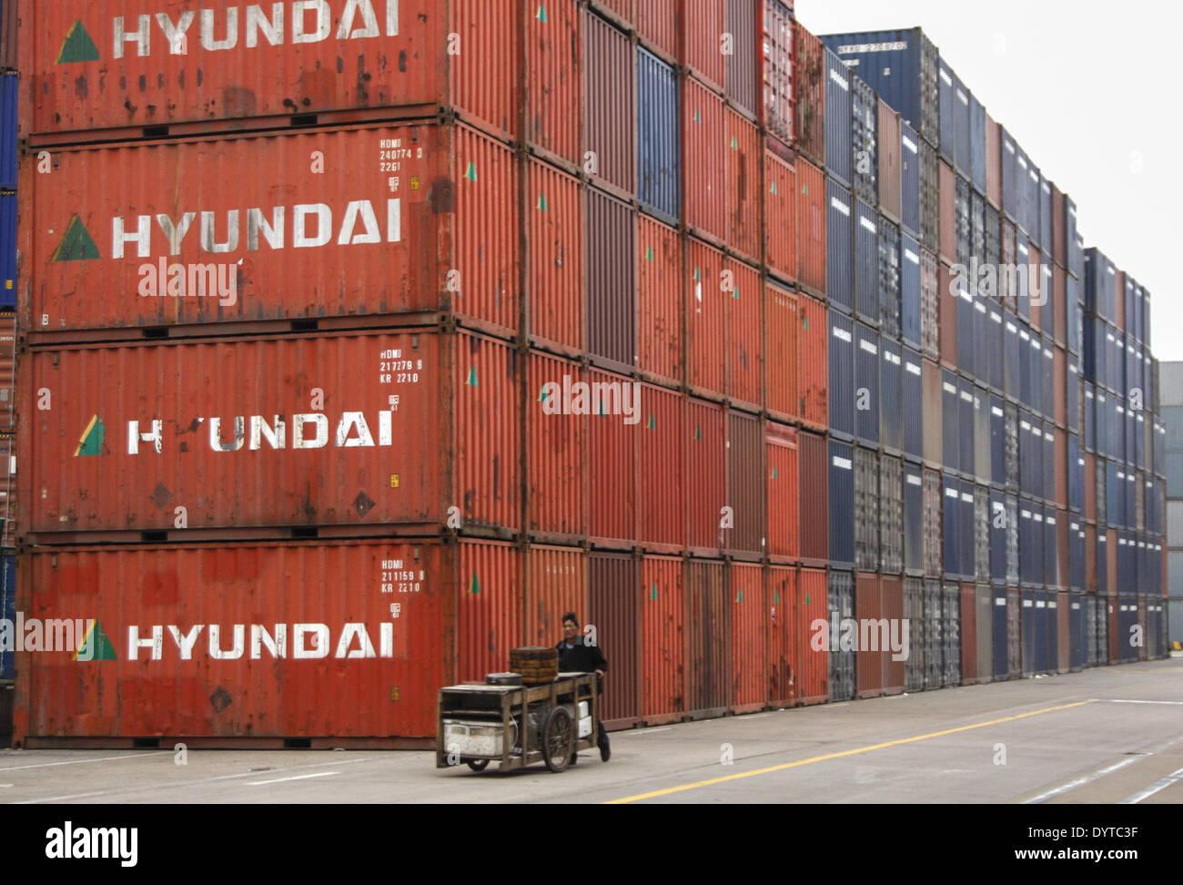 Un vendeur de rue pousse son panier passe par des conteneurs dans un port de conteneurs du salon à Shanghai Banque D'Images