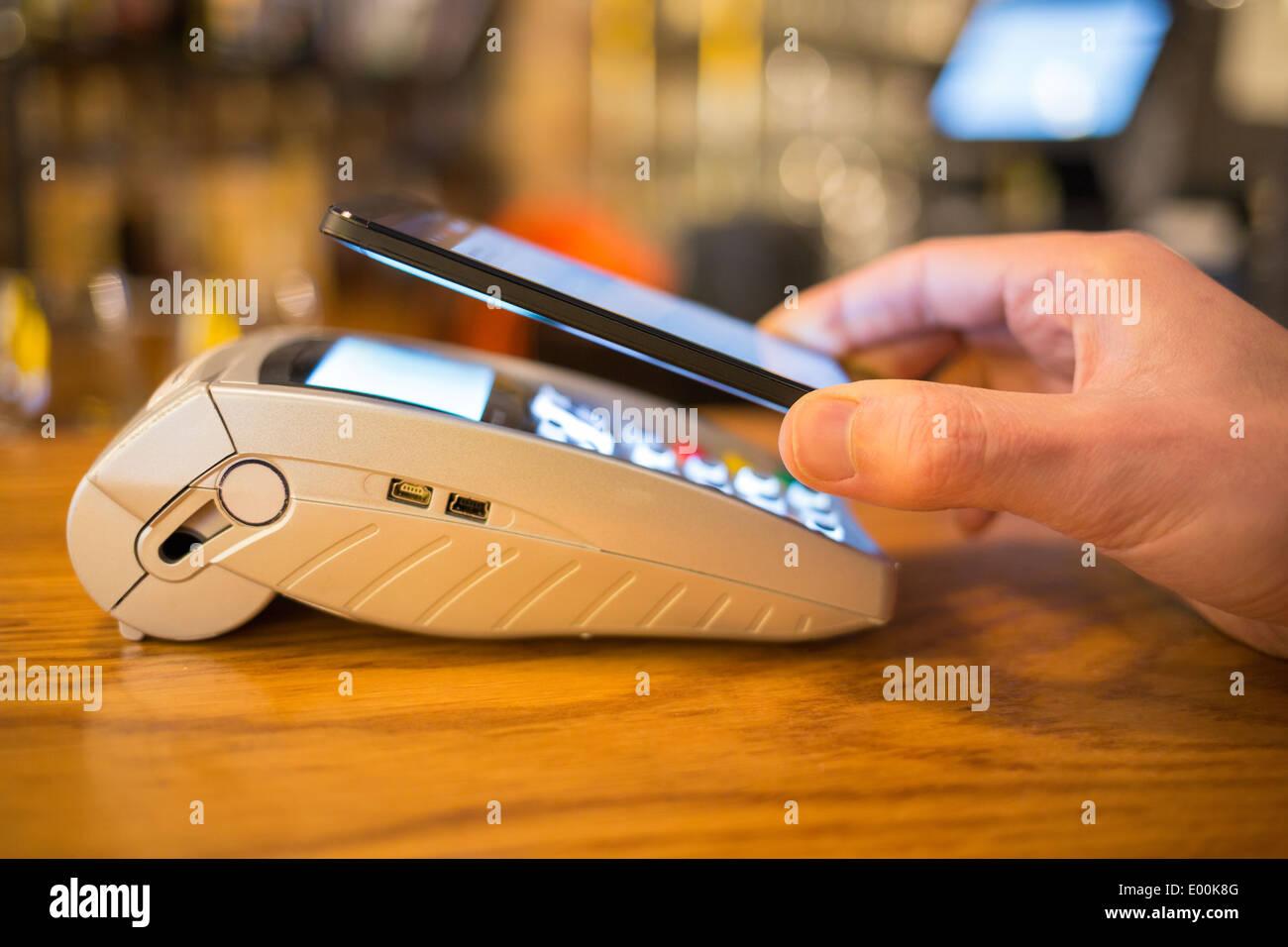 La main des hommes wallet smartphone boutique paiement Photo Stock