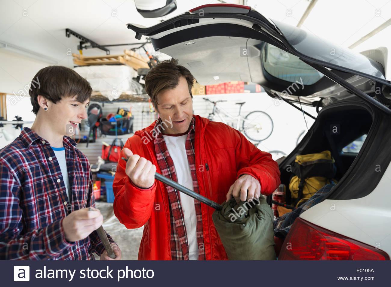 Père et fils le chargement d'équipement de camping en location Banque D'Images