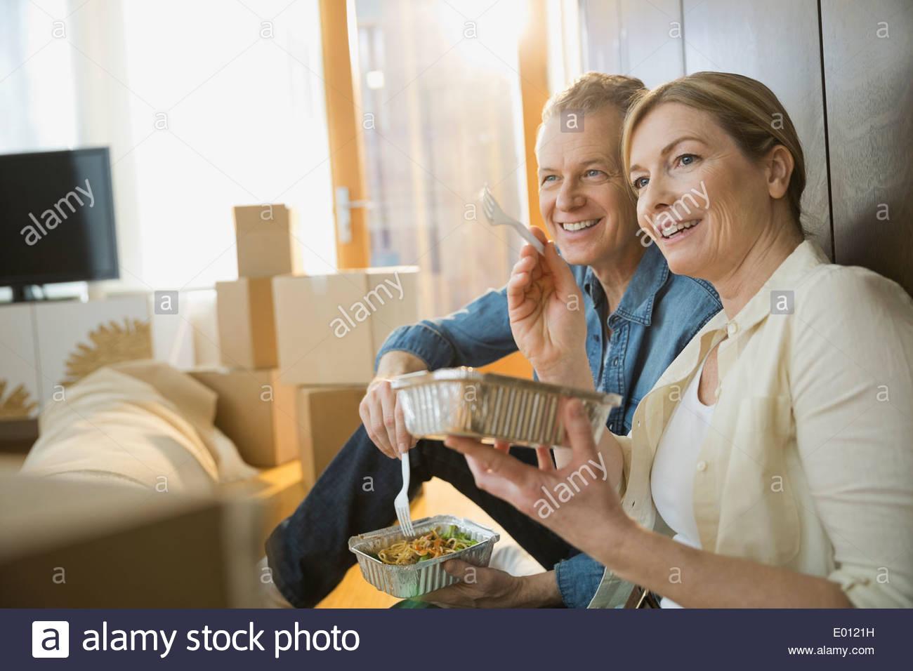 Couple eating take out food près de cartons de déménagement Photo Stock