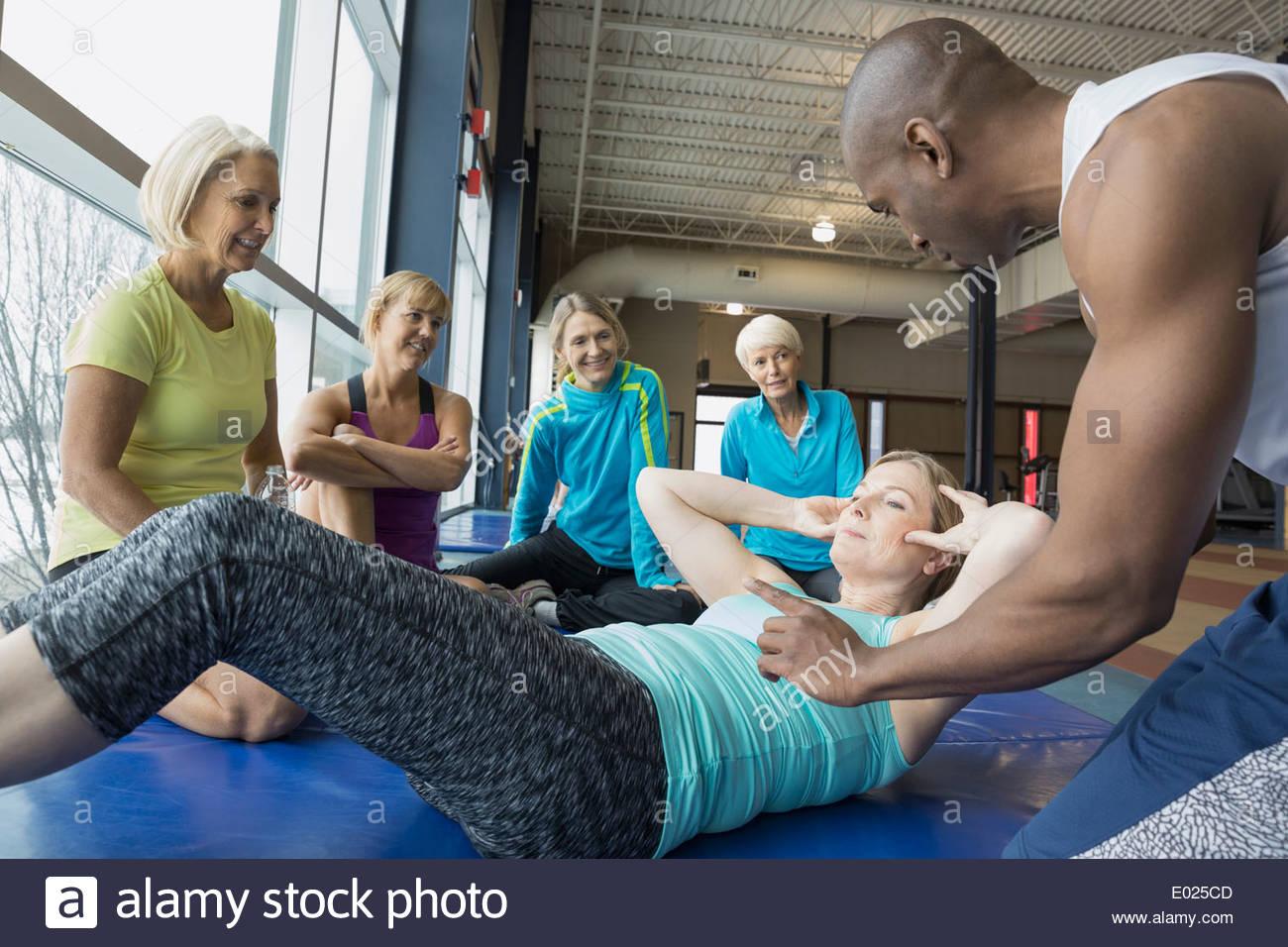 Entraîneur personnel woman甄s directeurs sit-ups at gym Photo Stock