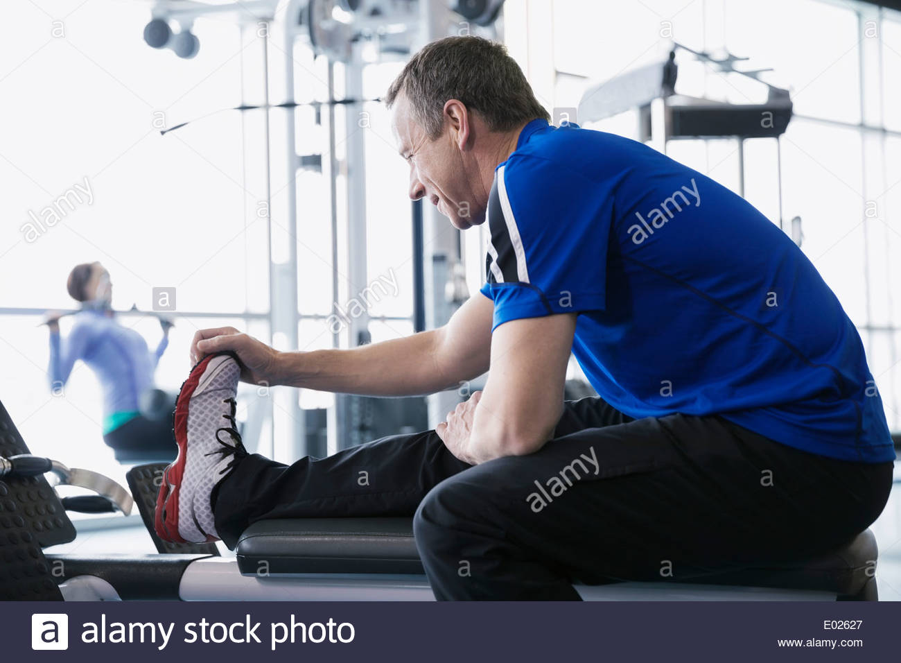 Man stretching leg at gym Photo Stock
