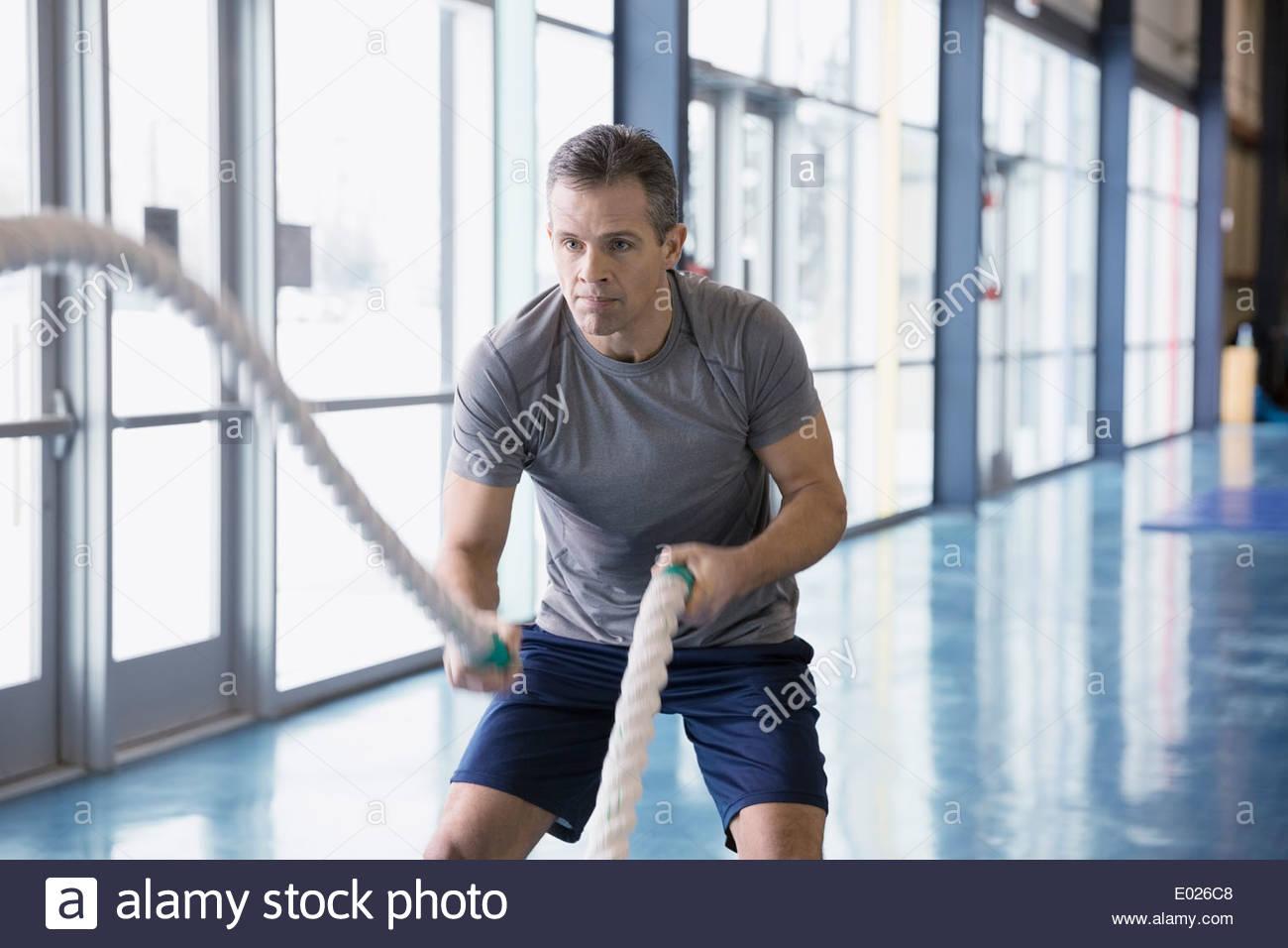 La formation de l'homme avec des cordes à gym Photo Stock