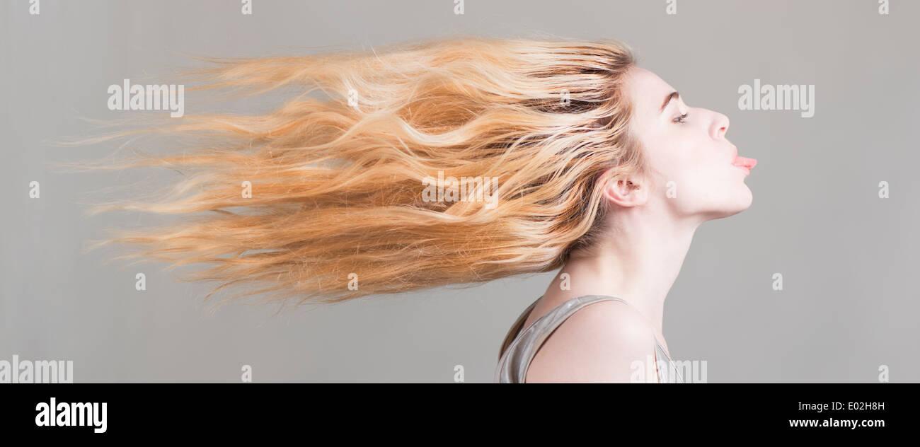 Femme blonde aux cheveux longs battant coller sa langue dehors. Image conceptuelle de la liberté, l'attitude et la personnalité forte. Photo Stock
