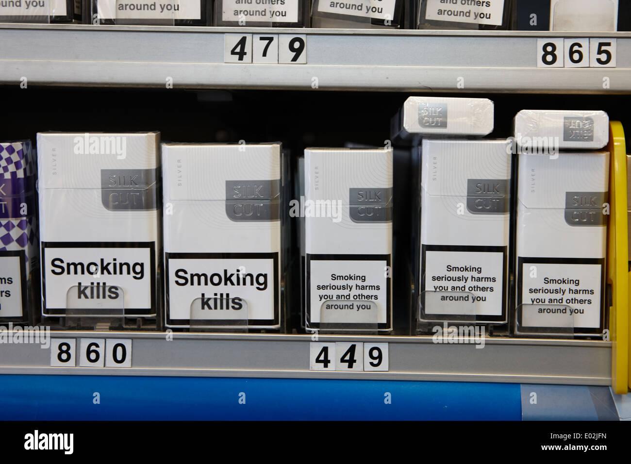 Les marques de cigarettes dans un emballage avec des avertissements pour la santé au cabinet dans un petit magasin d'Irlande Photo Stock