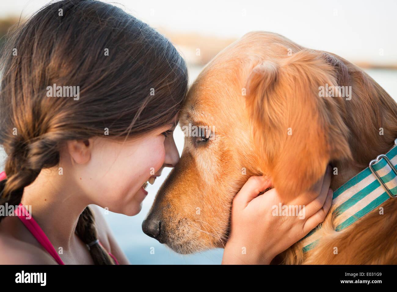 Une jeune fille et d'un golden retriever dog nez à nez. Photo Stock