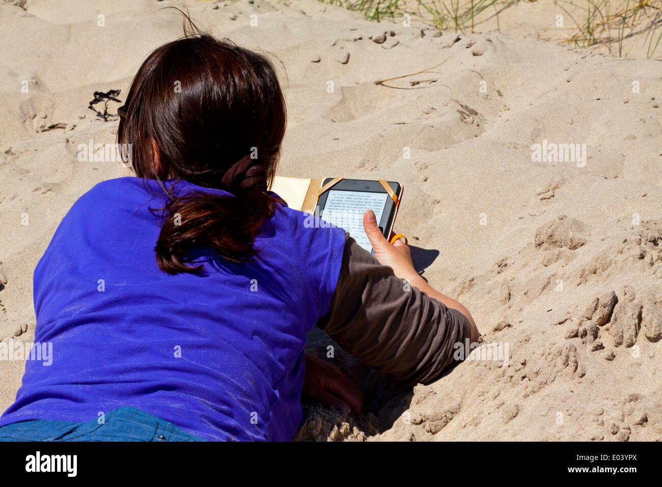 Femme allongée sur une plage de sable fin à l'aide d'un Amazon Kindle e-reader pour lire un livre tout en vous relaxant sur maison de vacances Photo Stock
