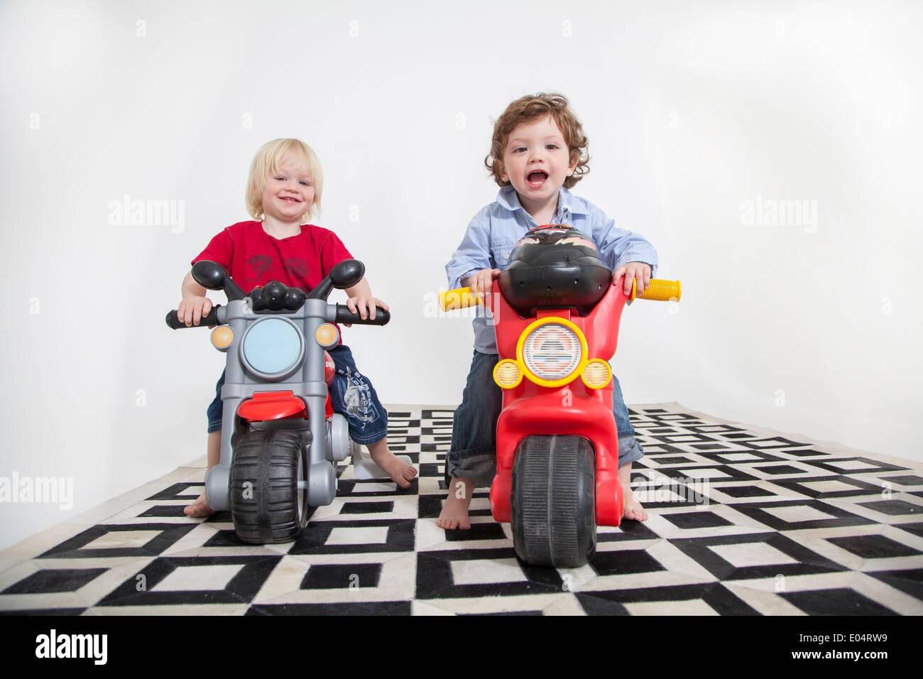 2 jeunes garçons jouent sur des scooters équitation vers la caméra, tourné en studio sur un tapis noir et blanc Photo Stock
