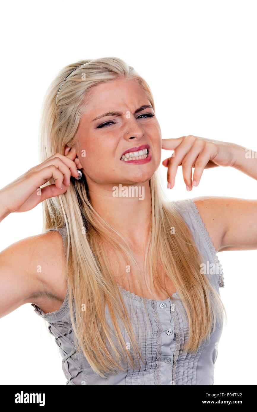 Jeune femme souffre de la pollution sonore, reste fermée à elle-même les oreilles., Junge Frau leidet unter, Laermbelaestigung haelt tr Photo Stock