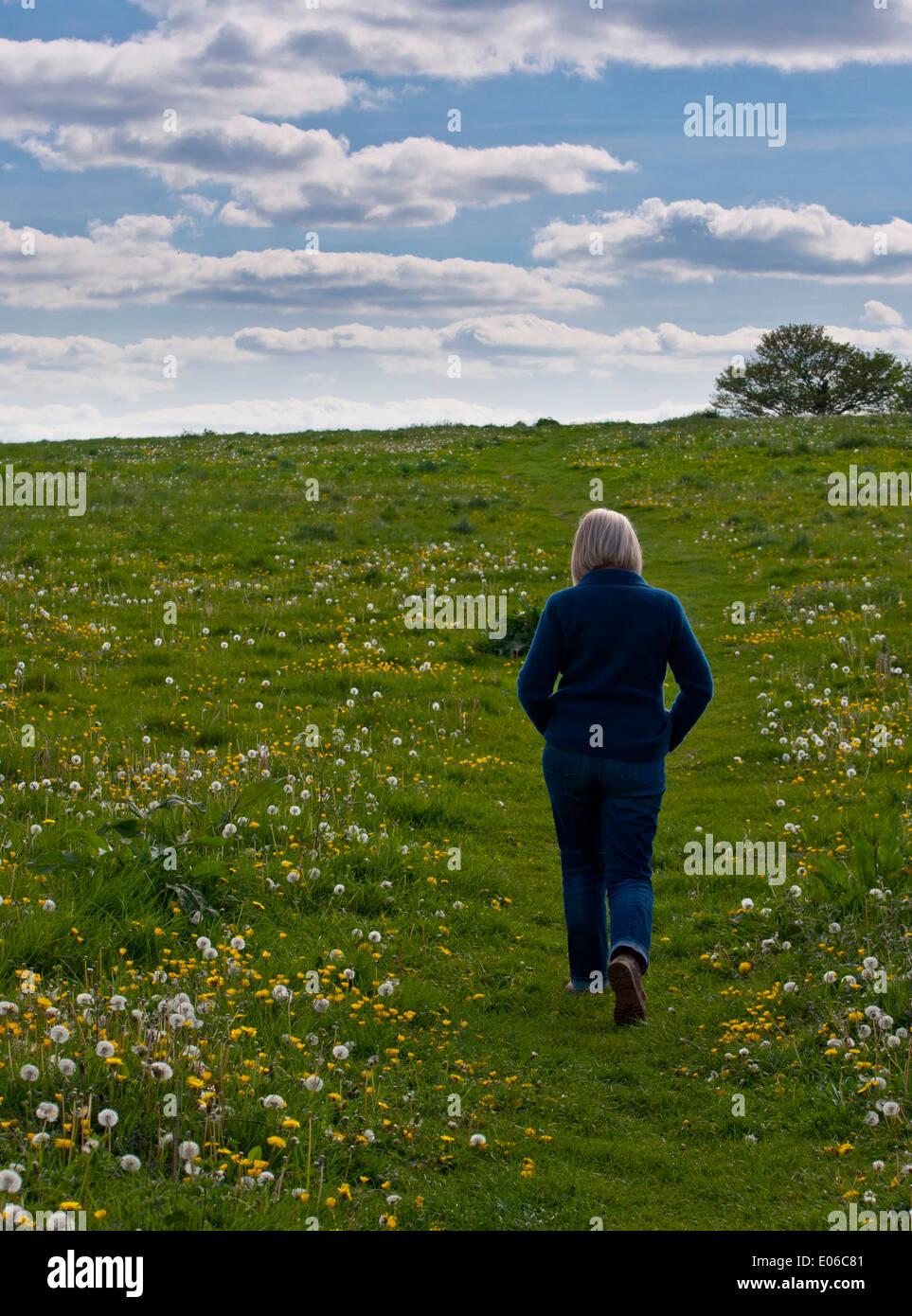 L'âge moyen anonyme femme femme marchant sur terrain Photo Stock