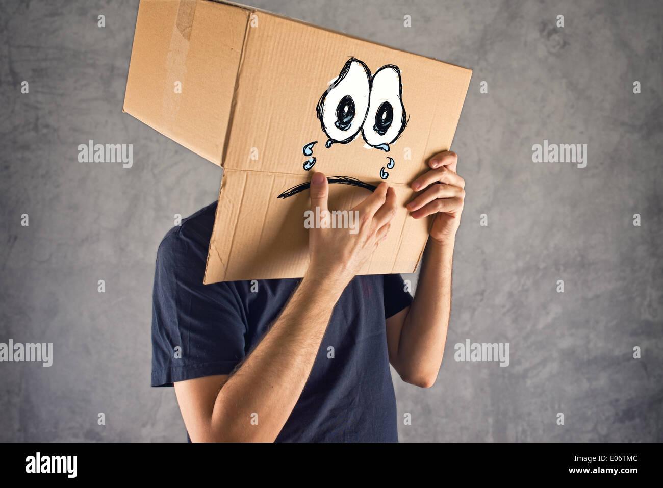 Homme avec boîte en carton sur la tête et visage pleurant triste expression. Concept de tristesse et dépression. Photo Stock