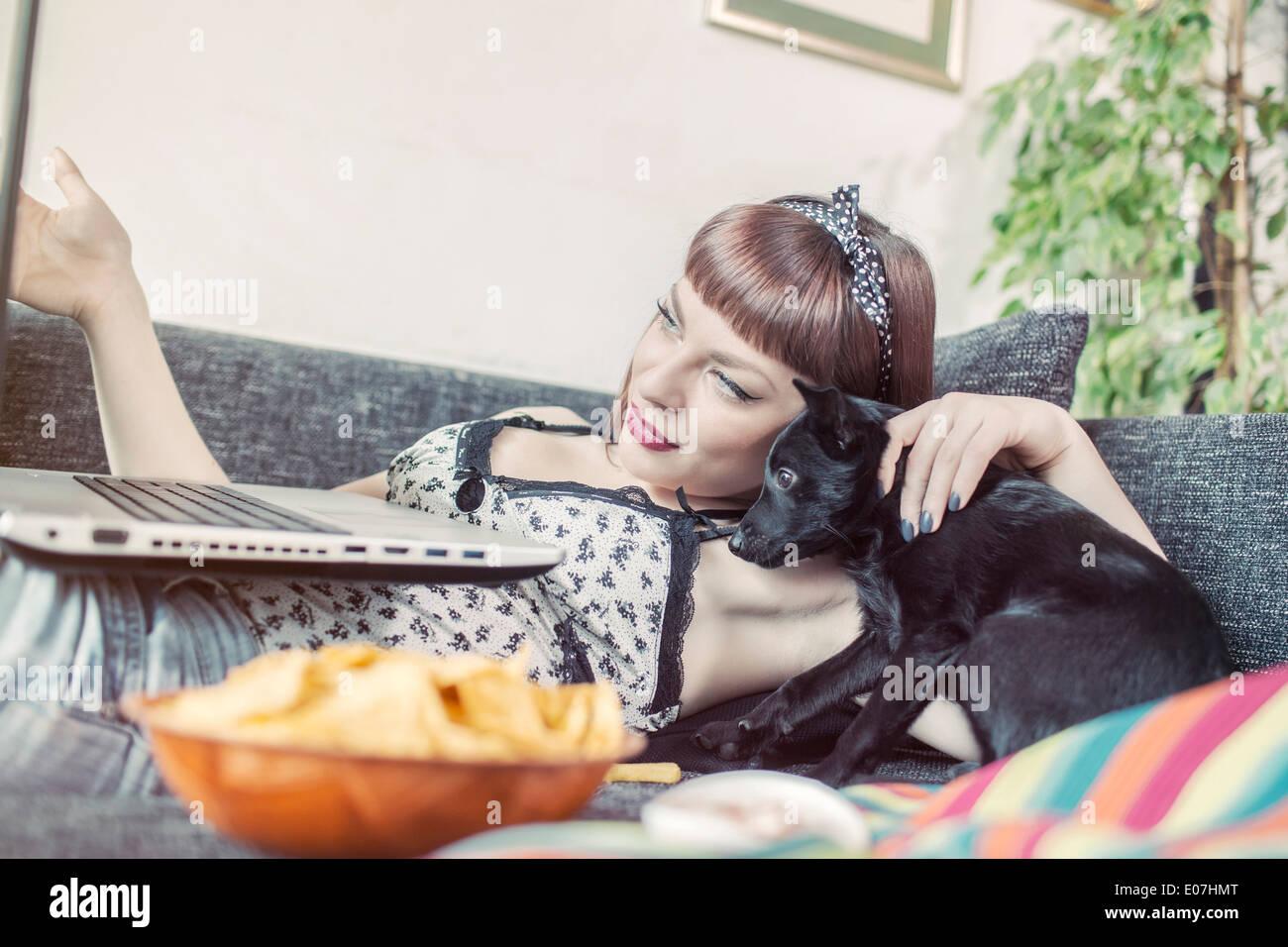 Young woman using laptop aux côtés de son chien de compagnie Photo Stock