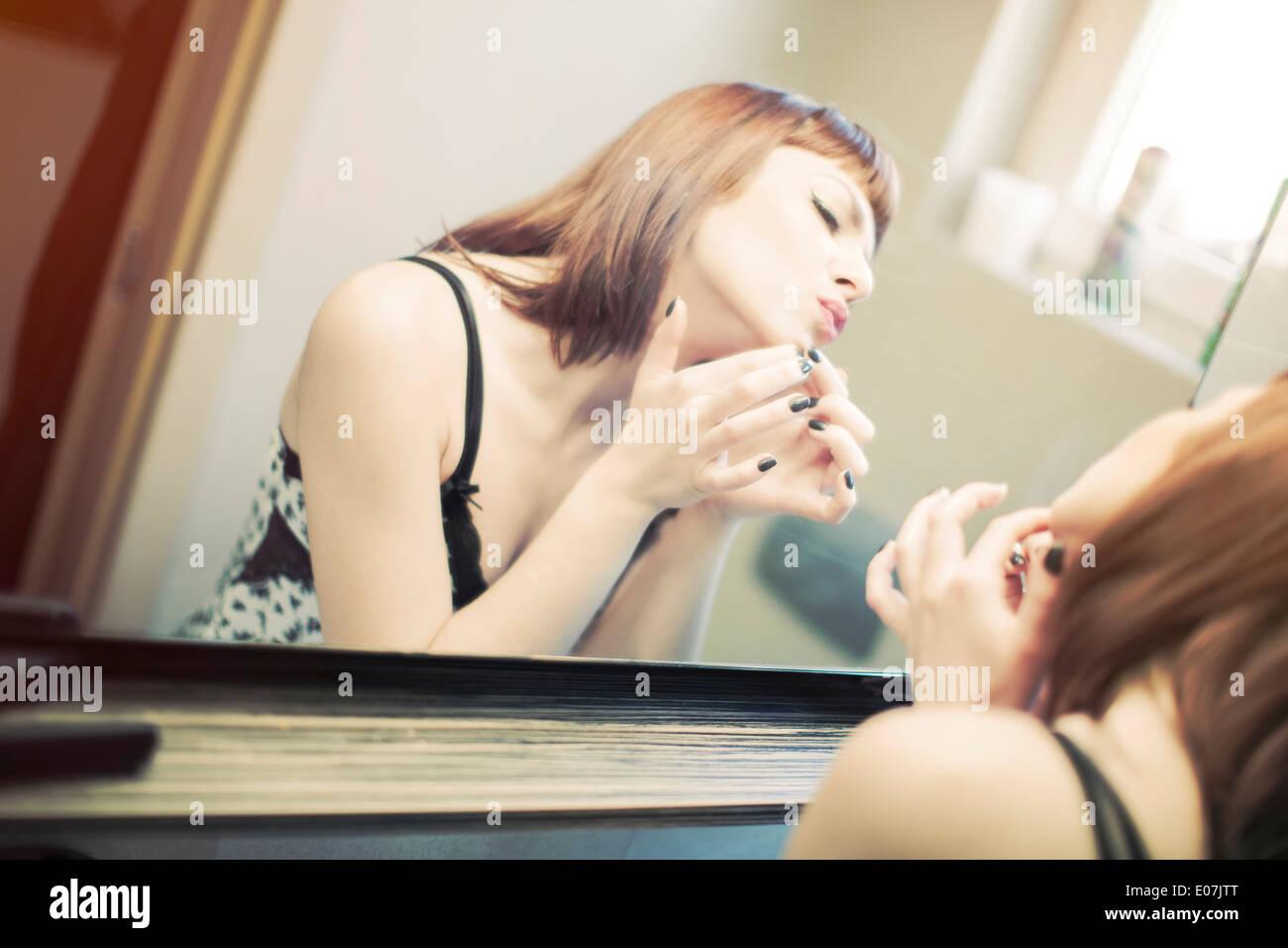 Jeune femme en nuisette devant un miroir Photo Stock