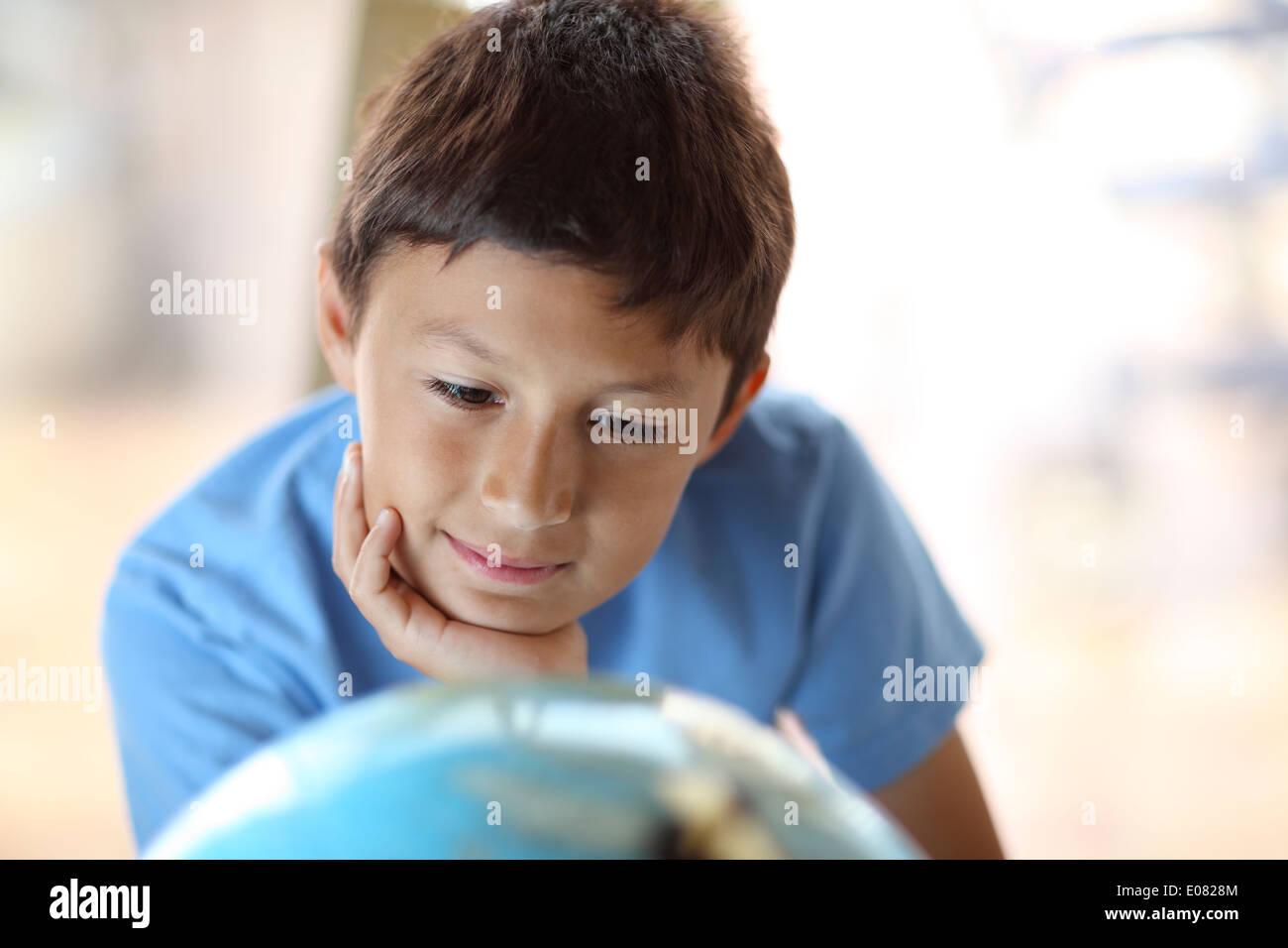 Y0Young boy rêve de parcourir comme il regarde un globe Photo Stock