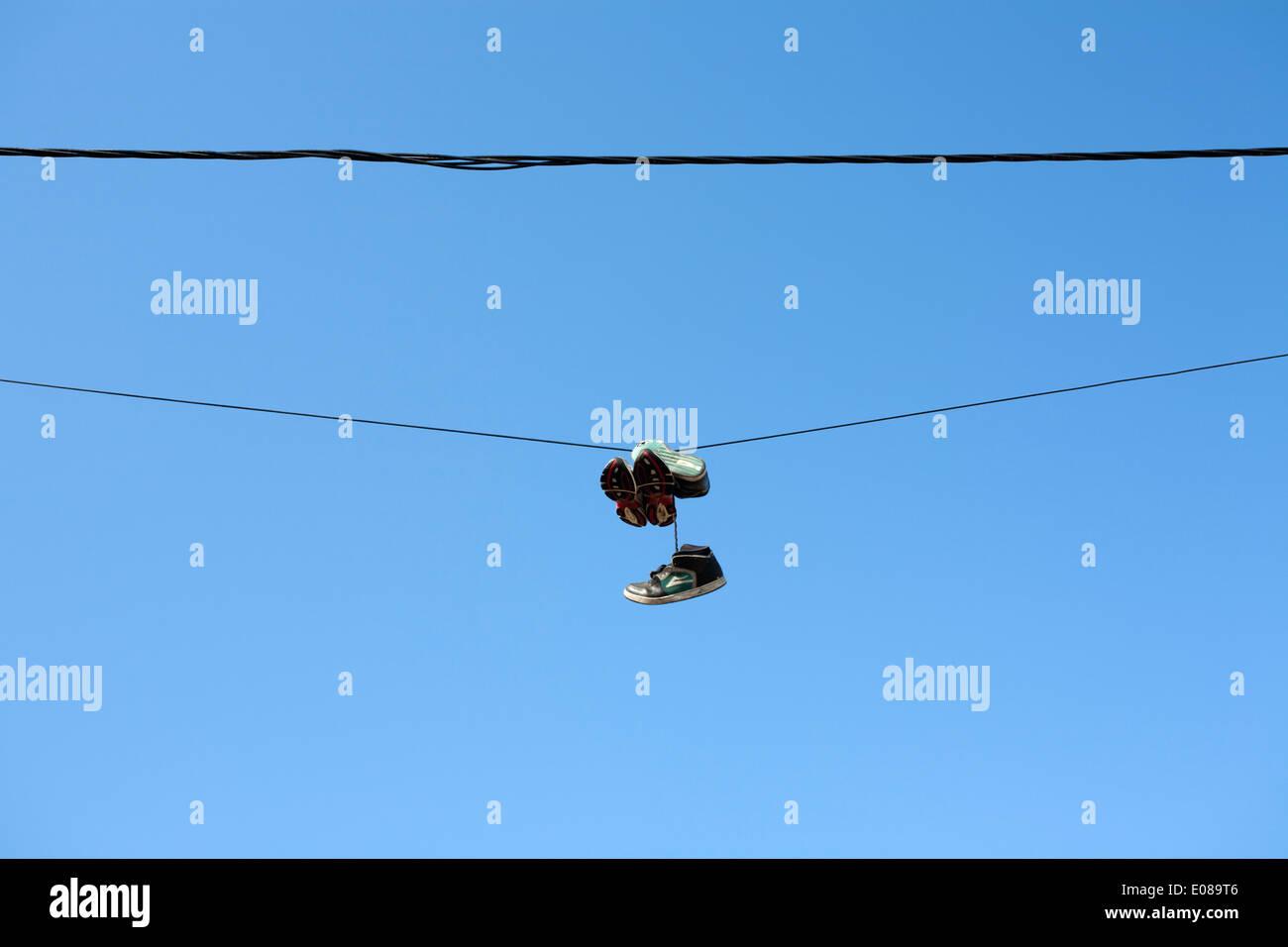 Deux paires de chaussures suspendu à un fil électrique Photo Stock