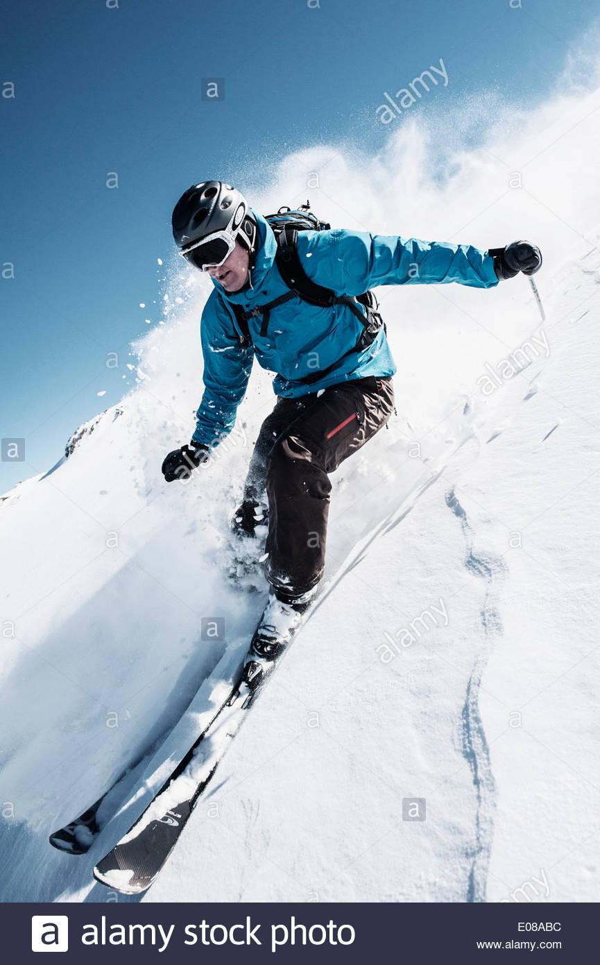 La longueur totale de l'homme skiing on mountain slope Photo Stock