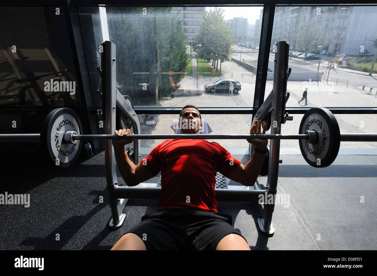 L'homme de faire des exercices de développé couché dans la salle de sport Photo Stock