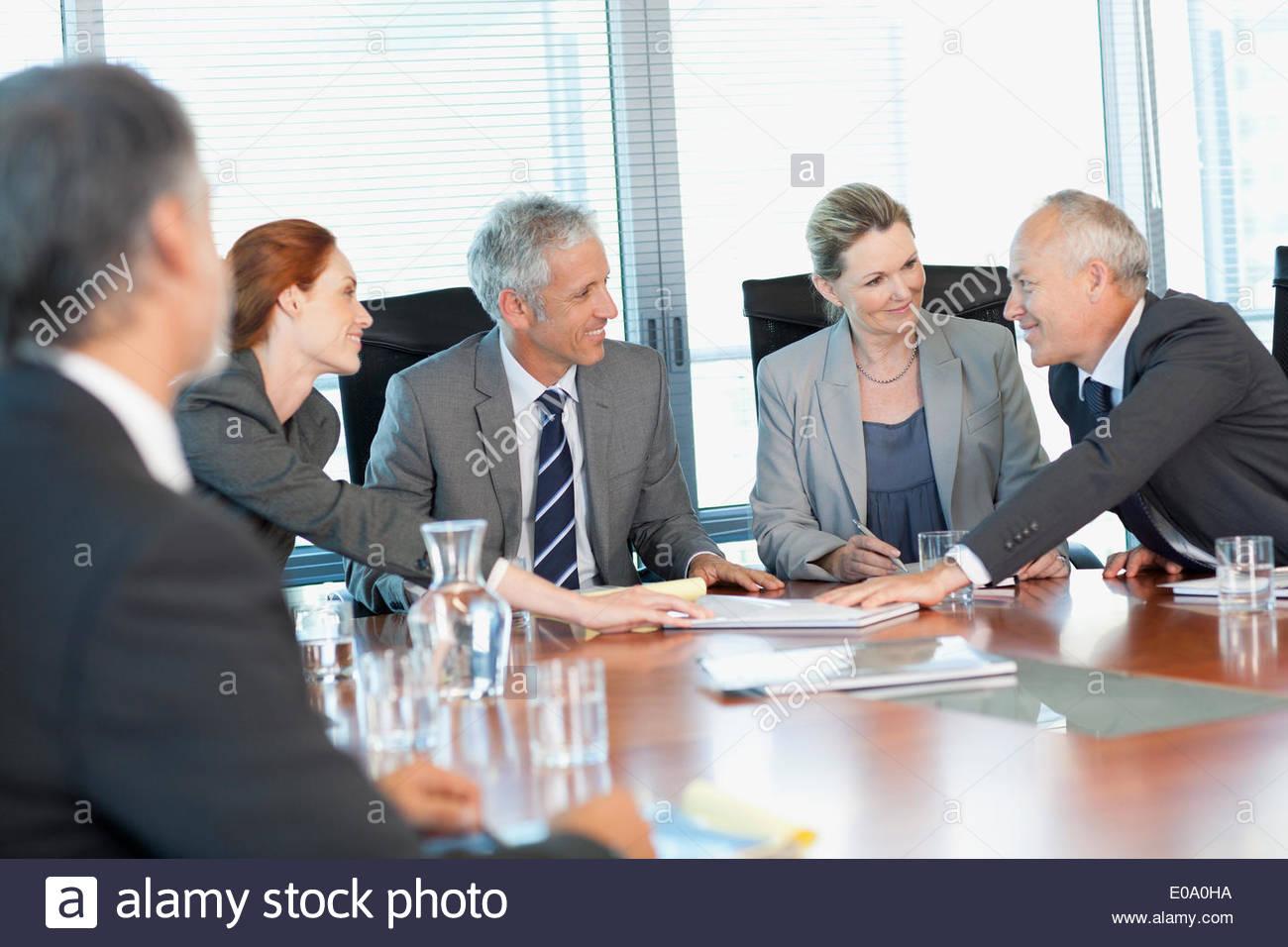 Smiling business people réunion à table dans la salle de conférence Photo Stock