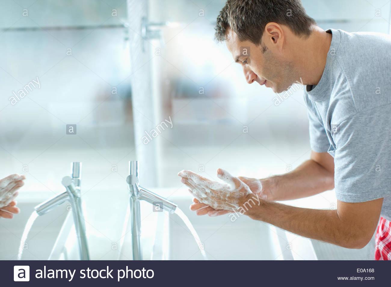 L'homme se laver les mains dans la salle de bains Photo Stock