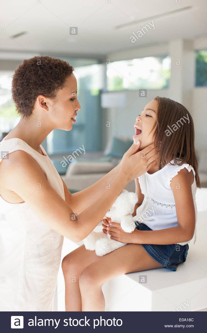 Femme malade contrôle la gorge de la Fille Photo Stock